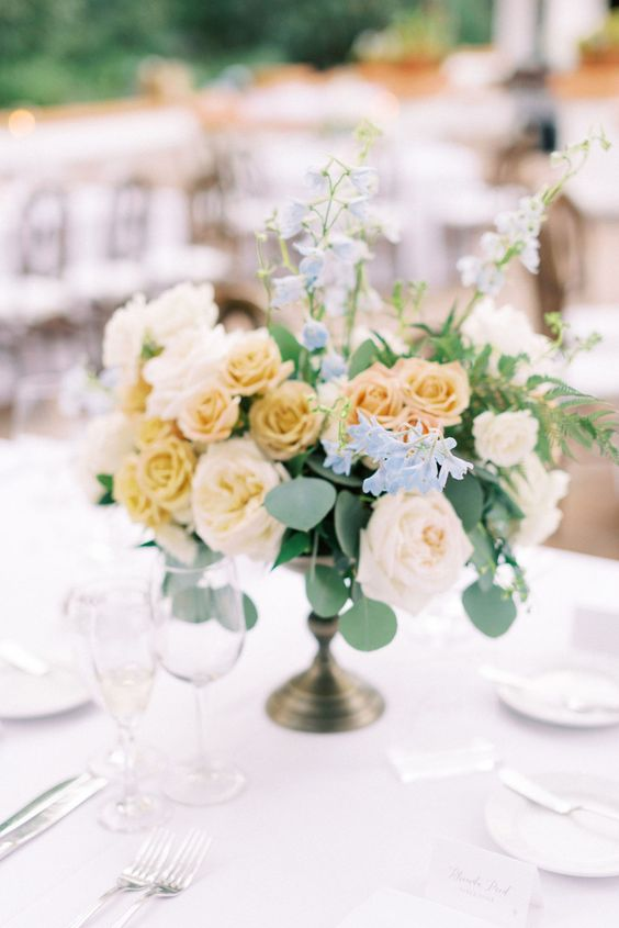 a refined secret garden wedding centerpiece of a bowl with neutral and yellow roses and some greenery is very chic