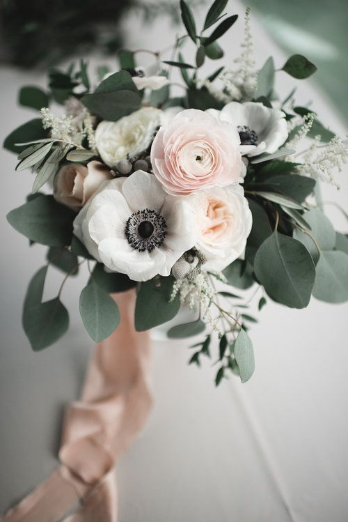 a refined wedding bouquet of blush ranunculus, white peony roses and white anemones, eucalyptus and blush ribbons is chic