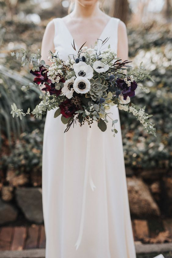 a refined wedding bouquet with dark blooms, white anemones, succulents, greenery and some blooming branches is gorgeous