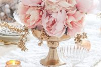 a refined wedding centerpiece of a gold bowl and lush pink peonies plus candles around is a very beautiful summer wedding idea