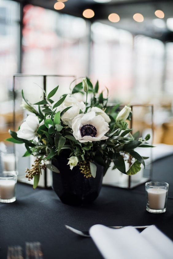 a refined wedding centerpiece of white anemones and eucalyptus in a black vase, with candles around is perfect for a modern wedding