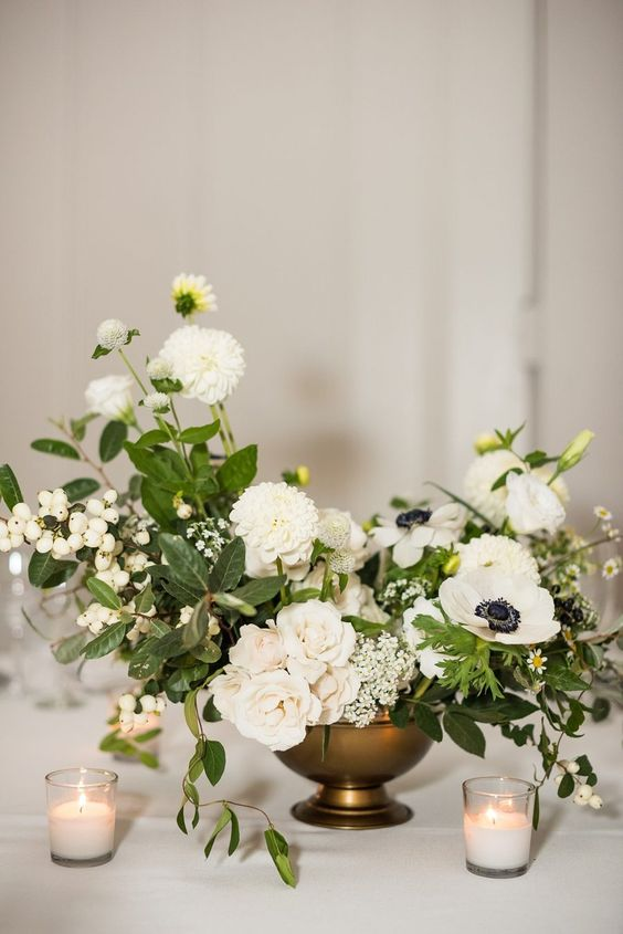 a refined wedding centerpiece of white blooms of various kinds including anemones, greenery and berries and candles around is very cool