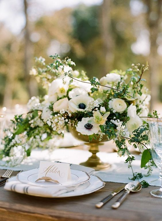 a refined wedding centerpiece of white ranunculus, anemones, blooming branches and greenery in a chic gilded bowl is perfect for spring or summer