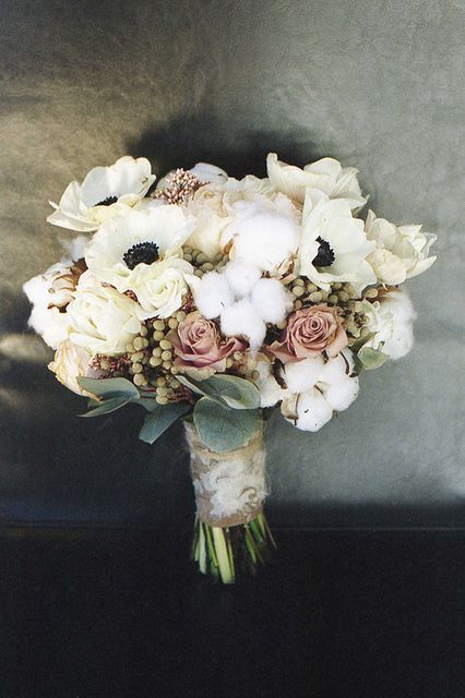 a refined winter wedding bouquet of white anemones, cotton, berrries, dusty pink roses and pale leaves with a burlap wrap