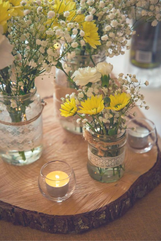a relaxed rustic wedding centerpiece of a wood slice, candles, jars wrapped with lace, baby's breath, yellow daisies and white carnations