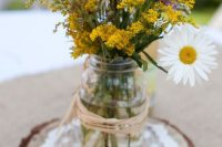 a relaxed rustic wedding centerpiece that includes chamomiles and wildflowers, a jar placed on a wood slice and a doily