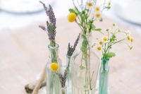 a relaxed wedding centerpiece of bottles and vases with lavender and daisies, billy balls and driftwood for a boho wedding