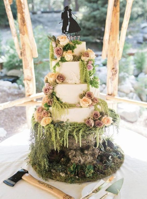 a romantic enchanted forest wedding cake with white tiers decorated with peachy and mauve blooms and greenery plus silhouette toppers