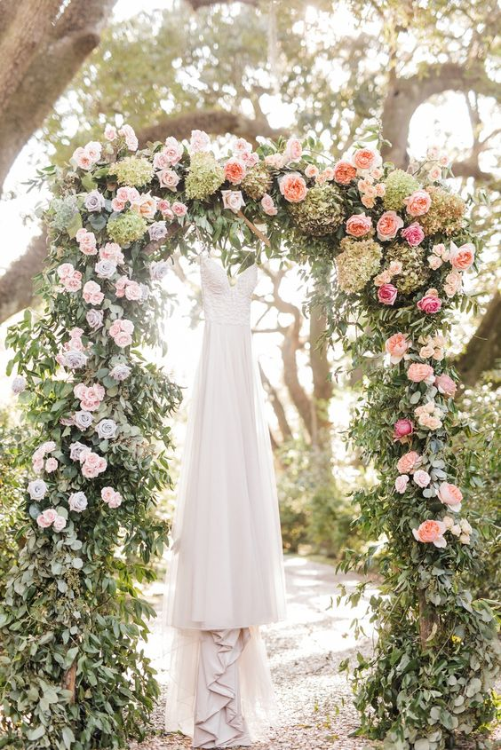 a romantic garden wedding arch with greenery, pink, peachy and green blooms is a very beautiful and classic idea