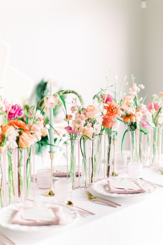 a romantic modern secret garden wedding centerpiece of sheer vases with super bright blooms and some greenery and colorful candles