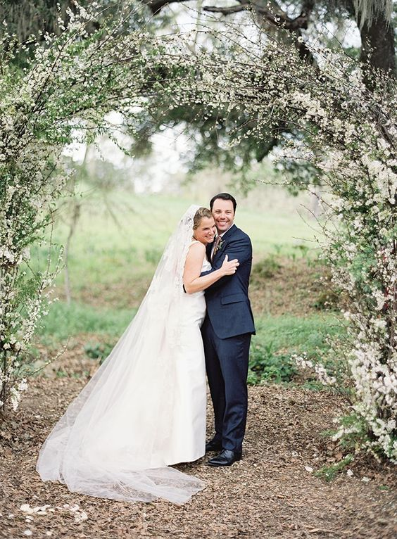 a romantic spring garden wedding arch covered with greenery and blooming branches looks fabulous and screams blooming and love
