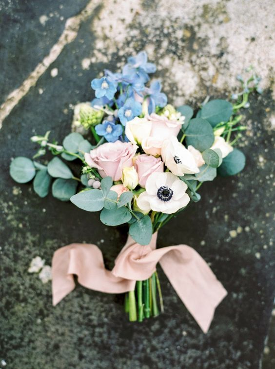 a romantic wedding bouquet of white anemones, pink roses, blue blooms and eucalyptus and blush ribbons is great for spring or summer