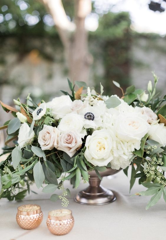 a romantic wedding centerpiece of a dark bowl, white and blush roses, white anemones and greenery plus candles around