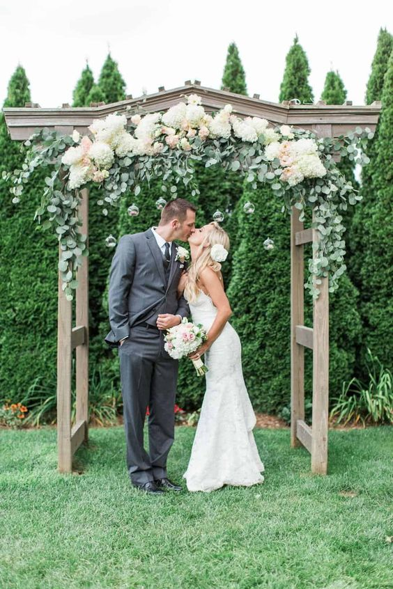 a rustic wedding altar covered with eucalyptus, white hydrangeas and blush blooms is a stylish idea for a summer wedding
