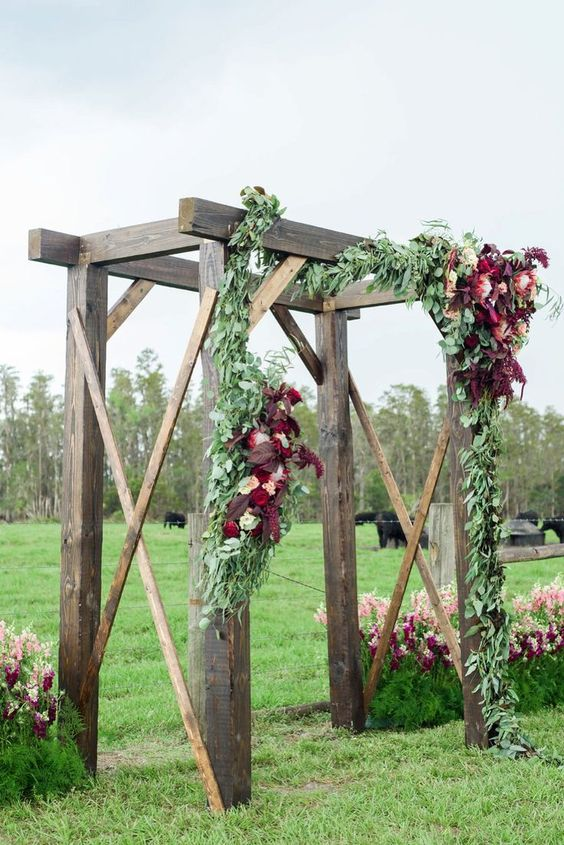 a rustic wedding arch decorated with greenery, blush and burgundy blooms is a lovely idea for a fall rustic wedding