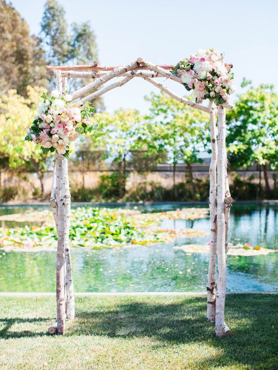 a rustic wedding arch of birch branches, pastel blooms and greenery with a backdrop of a pond is a lvoely idea for summer
