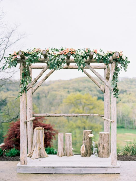a rustic wedding arch with tree stumps, greenery and peachy blooms plus a view of a fall forest for an autumn rustic wedding