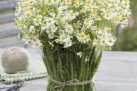 a rustic wedding arrangement with daisies in a vase and wheat covering the vase is a very simple and relaxed summer wedding idea