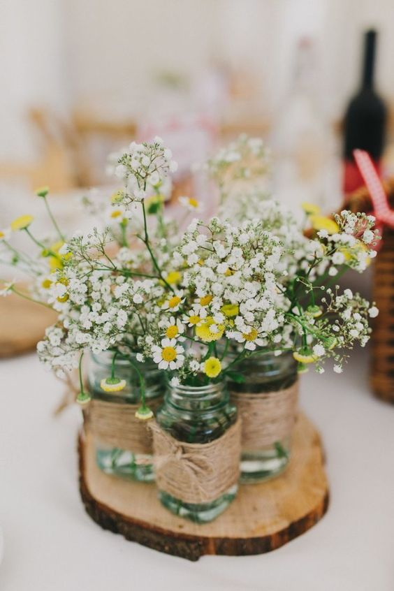 a rustic wedding centerpiece of a wood slice, jars wrapped with twine, daisies and baby's breath is a very cozy idea