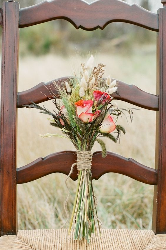 a rustic wedding mini bouquet with red roses, dried grasses and greenery with a twine wrap is a very cool and simple arrangement to make yourself