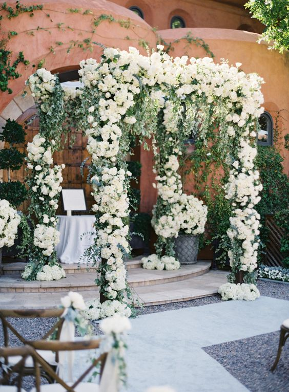 a secret garden wedding altar decorated with greenery and white blooms and with blooms at the base is a very chic and stylish solution