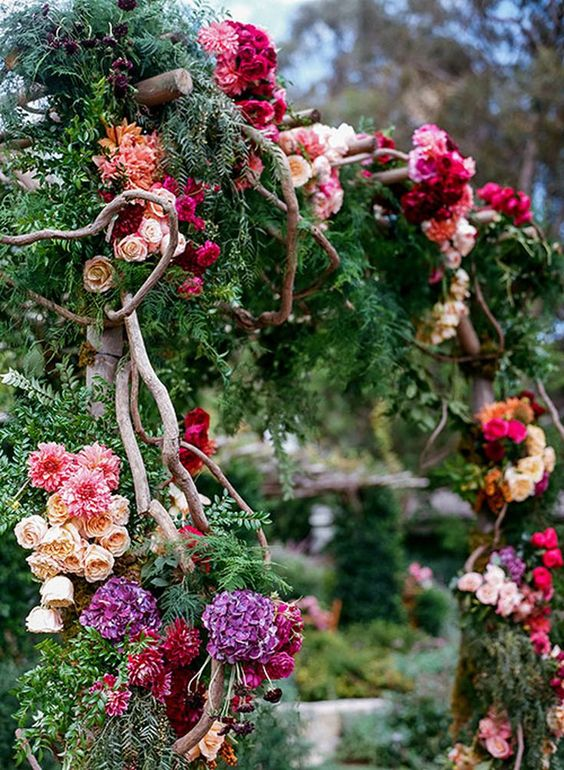 a secret garden wedding arch decorated with greenery and evergreens, bold blooms in hot pink, purple, burgundy, blush blooms and branches weaving the arch