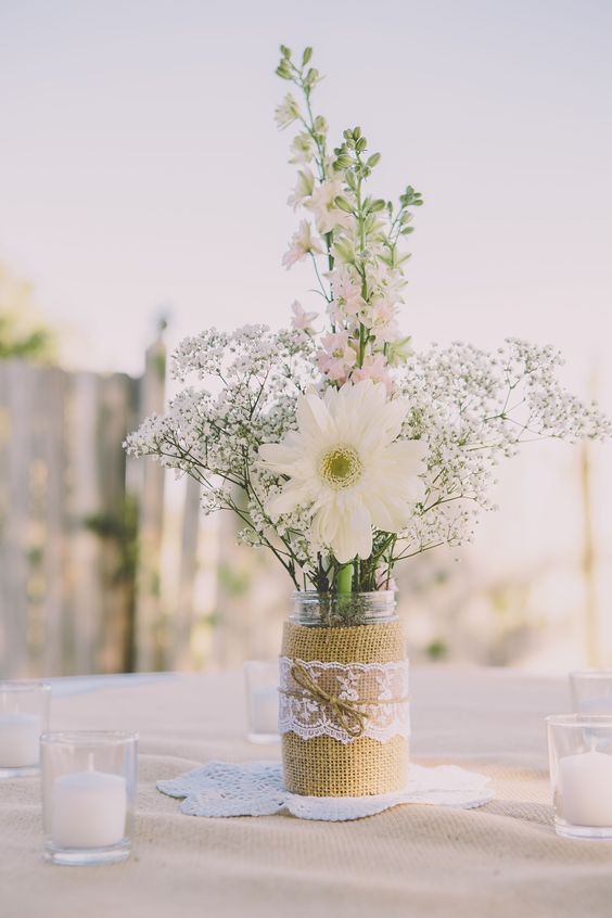 a simple and lovely rustic wedding centerpiece of baby's breath, pink delphinium and white daisies in a jar with a burlap and lace wrap