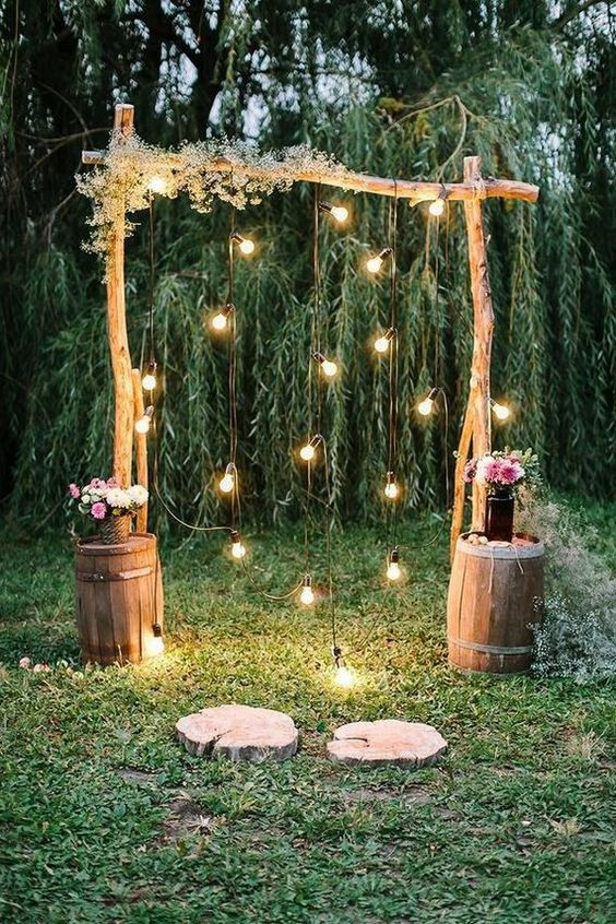 a simple rustic wedding arch of wooden branches, some baby's breath, lights, pink floral arrangements on barrels next to the arch
