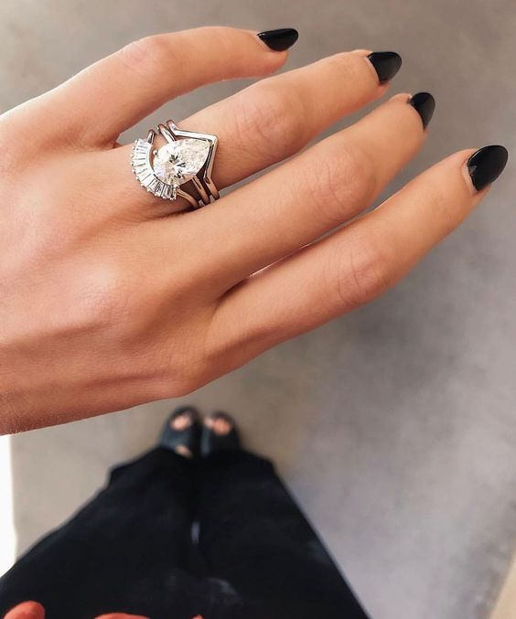 a sophisticated and modern stacked engagement ring with a large pear-shaped diamond, a triangle upper band and an arched diamond lower one