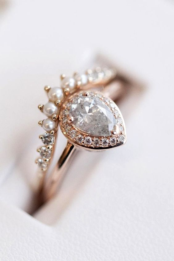 a sophisticated rose gold stacked engagement ring with a pear-shaped diamond framed with mini diamonds and with an arched diamond and pearl ring