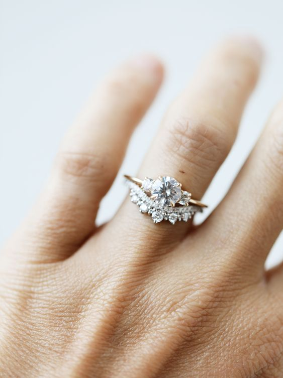 a sophisticated stacked wedding ring with a central round one and an arched diamond lower ring to frame it is chic and cool