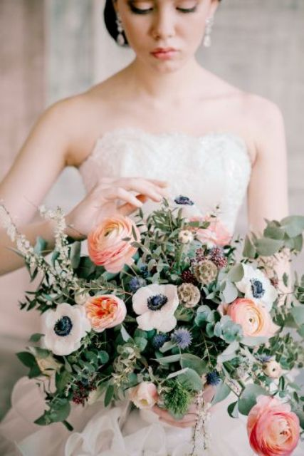 a sophisticated summer wedding bouquet with lots of eucalyptus, peachy peonies and ranunculus, white anemones, allium