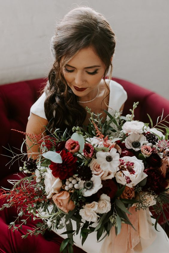 a statement fall wedding bouquet of burgundy blooms, rust roses, white anemones and peonies, greenery and dark blooms