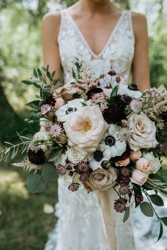 a statement wedding bouquet of dark blooms, blush and dusty pink roses, white anemones, various types of greenery will make an impression