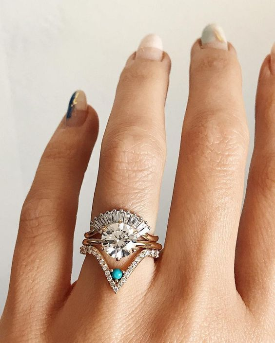 a stunning stacked wedding ring with a triangle lower ring and a turquoise piece, a central ring with a round diamond, an arched diamond upper ring
