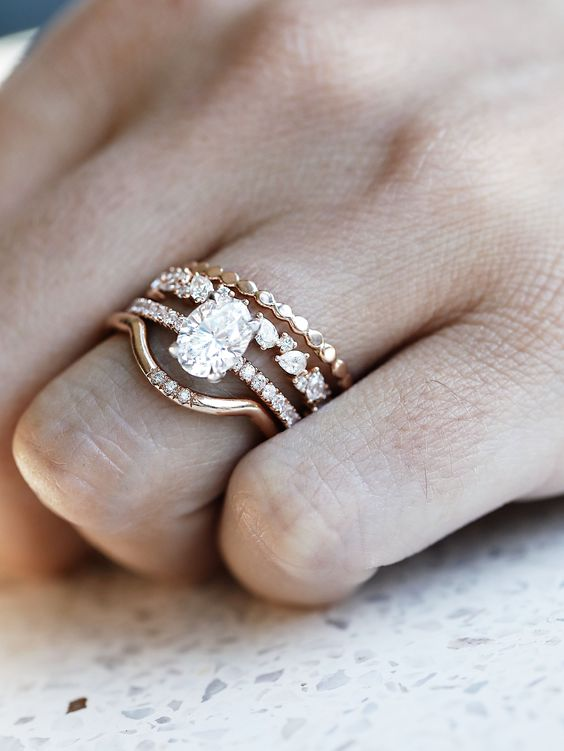 a stunning wedding ring stack with an oval shaped diamond, two lower rings with smaller diamonds and no diamonds and an arched upper ring with some rhinestones