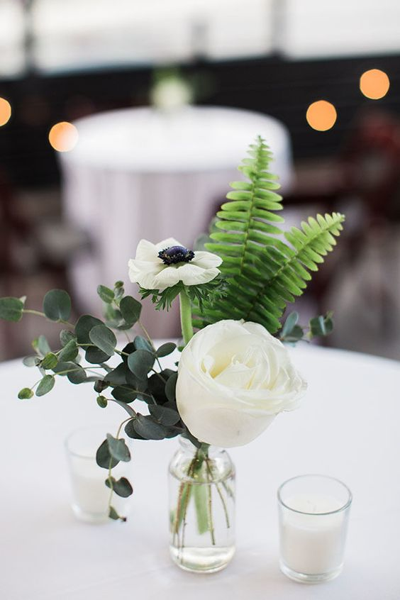 a stylish and simple wedding centerpiece of a vase with a white rose and ranunculus, some eucalyptus and fern and candles around