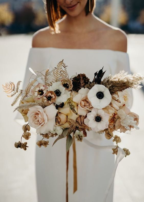 a stylish modern wedding bouquet of white anemones, blush and rust roses, dried blooms, leaves and grasses and mustard ribbons
