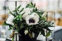 a stylish modern wedding centerpiece of eucalyptus and white anemones in a black vase is a very bold and easy idea