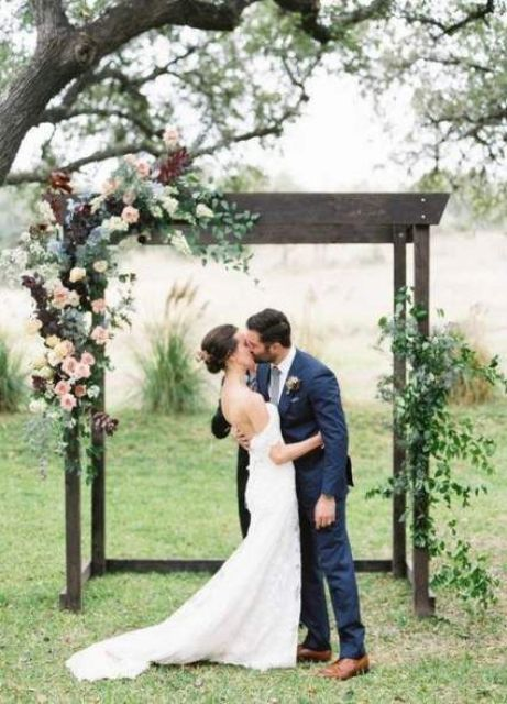 a stylish rustic wedding arch of dark wood, white, pink and burgundy blooms and greenery is a cool solution for a fall wedding