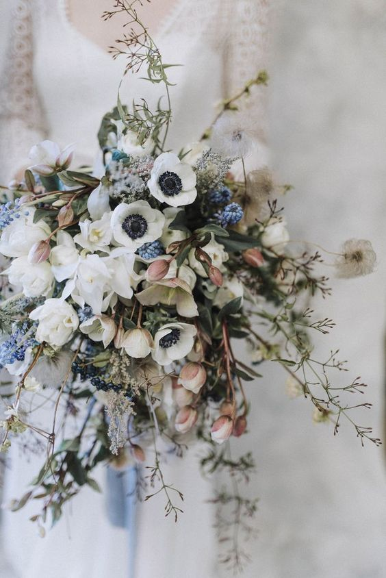 a stylish spring wedding bouquet of white anemones, various fresh spring blooms, branches and twigs is a chic idea with much dimension