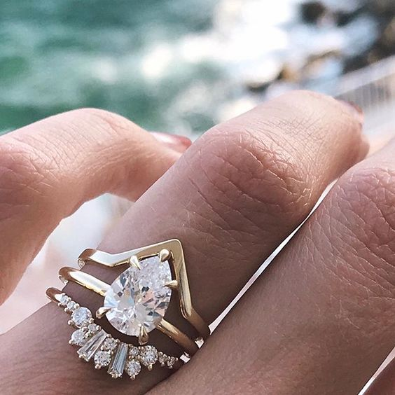 a stylish stacked wedding band with a central pear-shaped ring, a lower diamond one and a triangle gold band on top