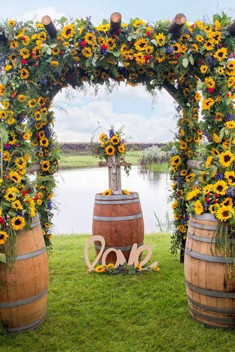 a super colorful summer rustic wedding arch covered with greenery, sunflowers, bold red and blue flowers and barrels at the base