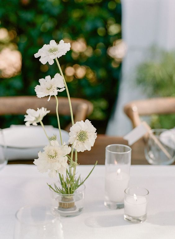 a super elegant wedding centerpiece of white blooms and white candles is a sophisticated idea for a spring or summer wedding