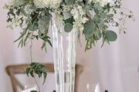 a tall wedding centerpiece of a sheer vase, white hydrangeas and various greenery and eucalyptus is chic and timeless