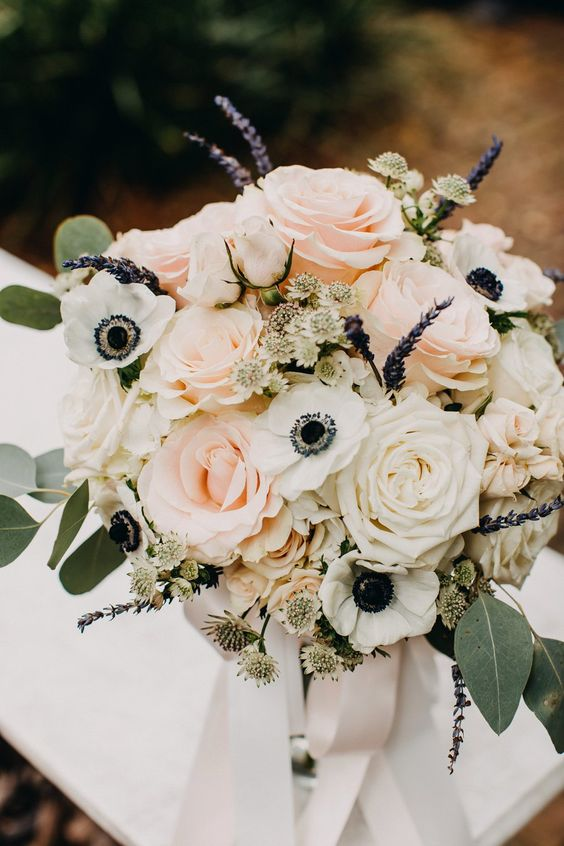 a tender wedding bouquet of white and blush roses, white anemones, lilac and greenery is amazing and beautiful