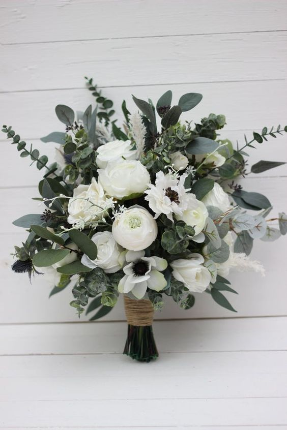 a textural wedding bouquet of white roses and peonies, white anemones and lots of textural eucalyptus looks wild