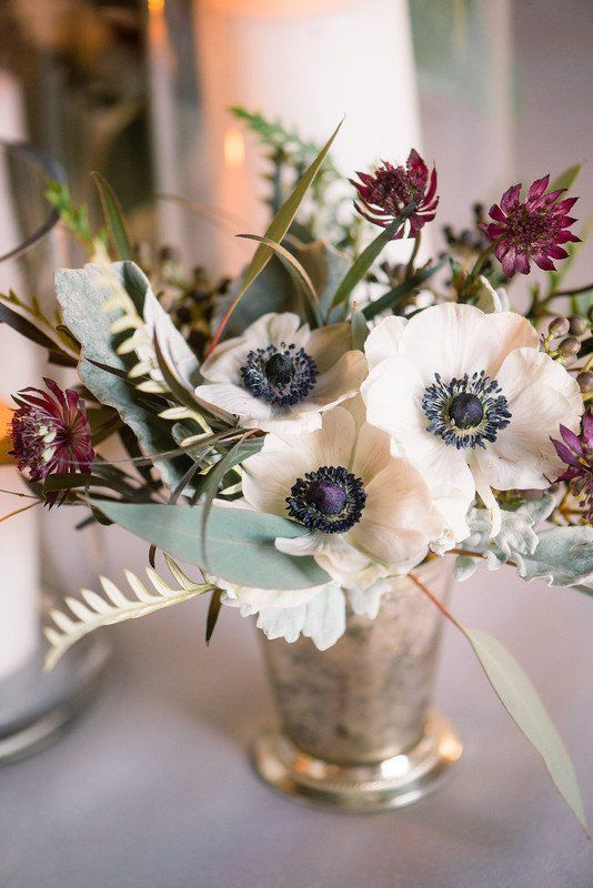 a textural wedding centerpiece of white anemones and dark burgundy blooms, foliage and pale leaves is a stylish idea for summer