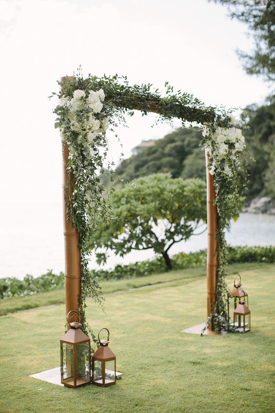 a traditional rustic wedding arch of brass pipes, greenert and white hydrangeas plus vintage candle lanterns around