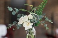 a very cool and easy wedding centerpiece of white roses, euclayptus and fern in a sheer vase and candles